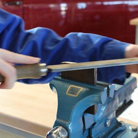 Bild eines Arbeiters, der ein in einen Schraubstock eingespanntes Metallstück feilt