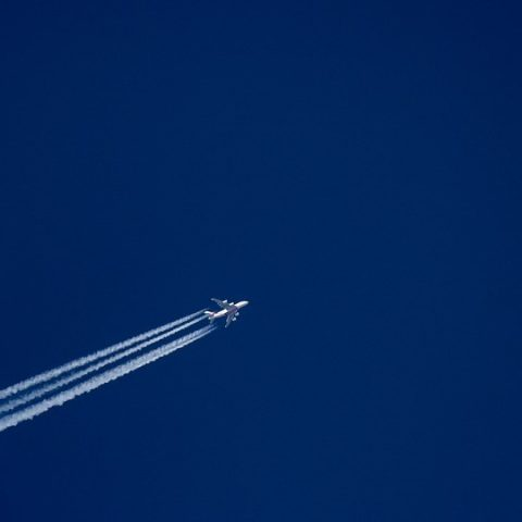 Flugzeug mit Kondensstreifen vor blauem Himmel